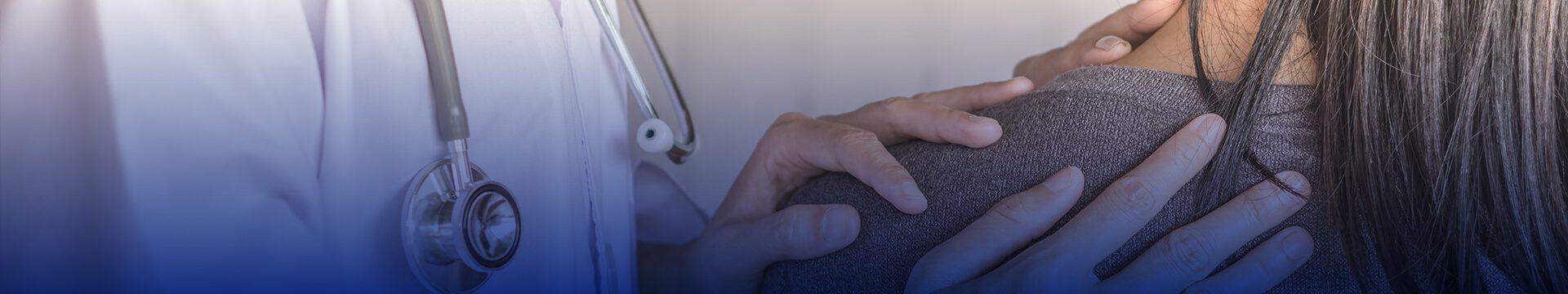 Healthcare provider's hands on patient's shoulder.