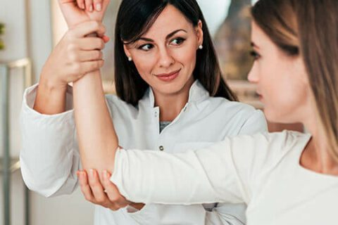 Healthcare professional evaluating a patient's arm.