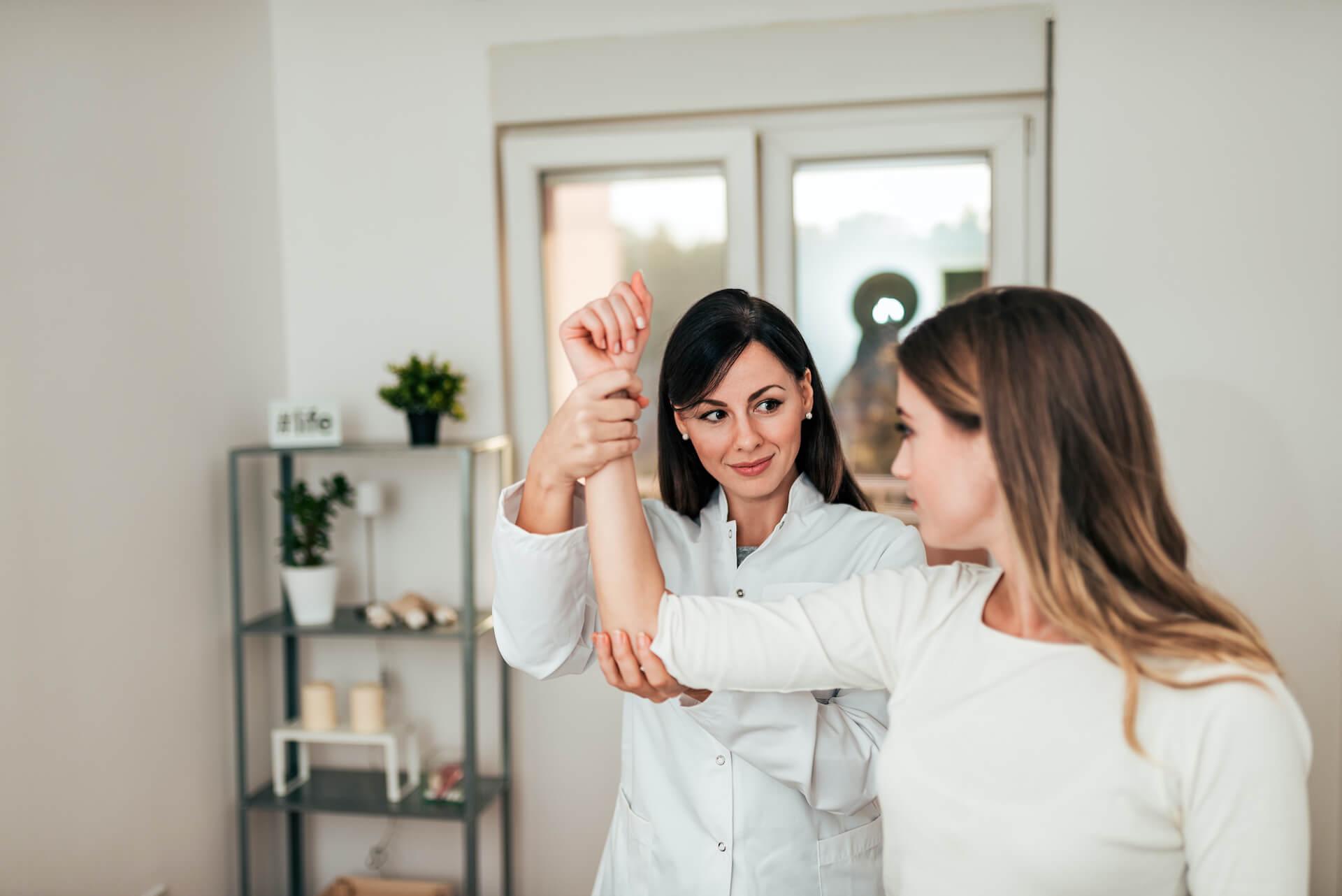 Healthcare professional evaluating a patient's arm.
